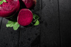 Red beets and leaves on a black background. Beetroot and mint juice in a glass. Luxurious vegan cocktails. Copy space. royalty free stock photo