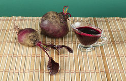 Red beets with leaves and jug with juice Stock Image