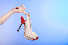 Red beige female shoes high heels in hands of woman on violet. Closeup of red beige female shoes boots high heels in hands of woman on violet studio shot Royalty Free Stock Photo