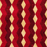 Red beige rhombus grunge background. Geometric pattern made of rhombuses in various bright reds and beige colors overlaid with grunge elements and scratches to Royalty Free Stock Photo