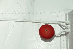 Red bell on boat hull painted white. Deail of passenger ship with red alarm bell on white boat hull stock photo