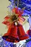 Red bell in the christmas tree. Pair of red christmas bells hanging by a golden cord Royalty Free Stock Photo