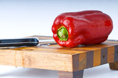 Red bell pepper. A red bell pepper and knife on a wood cutting board Stock Photography