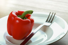Red bell pepper. On White dish with fork royalty free stock photography