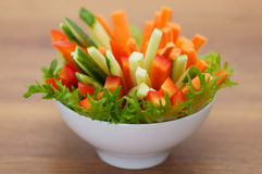 Red Bell pepper, cucumber and carrots straws with. Salad leaves  on wooden background Stock Photography