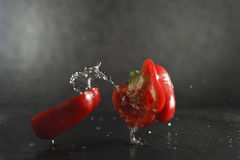 Red bell pepper dropped splashing water Stock Photo