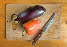Red bell pepper, eggplant and knife on wooden cutting board. Top view on kitchen table. Still life Royalty Free Stock Photos