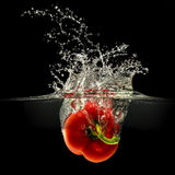 Red bell pepper falling in water on black Stock Photography