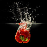 Red bell pepper falling in water on black Royalty Free Stock Photos