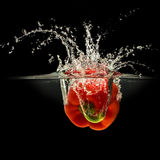 Red bell pepper falling in water with splash on black background Royalty Free Stock Photography