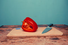 Red bell pepper and knife on chopping board Royalty Free Stock Photos