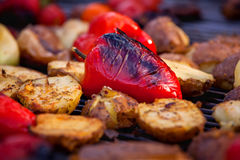 Red bell pepper and potatoes grilled until golden brown. The concept of proper nutrition and a healthy lifestyle. Cooking vegetables on the barbecue Royalty Free Stock Photos