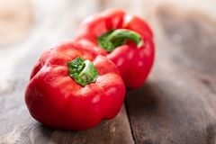 Red bell peppers or sweet peppers. On wooden background, fresh vegetables Stock Photos