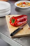 Red Bellpepper And Knife On Cutting Board Stock Image
