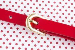 Red belt on polka dots Royalty Free Stock Image