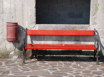 Red Bench and Bin. An old wooden bench painted bright red next to a small waste bin stock photos