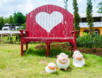 Red bench chair with heart symbol and sheep statue Royalty Free Stock Photo