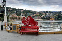 Red bench decorated with red hurts is staying on a street near coastline of sea Stock Photos