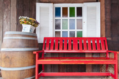 Red bench in front of multi colour glasses of window. Stock Photography