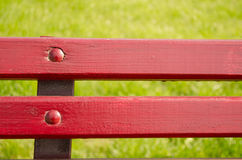 Red bench on the green grass. Part of red bench on a background of grass Stock Images