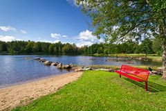 Red bench at the lake in Kyrkhult. Sweden Royalty Free Stock Photo