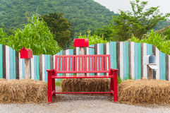 Red bench and mail boxes. In front of multi color fence Stock Images