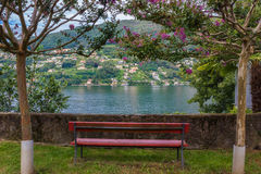 Red Bench Overlooking Lake Lugano in Switzerland. An empty bright red bench overlooking a peacefull view of Lake Lugano, Switzerland Stock Images