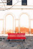 A red bench in a plaza of Venice, Italy. A bright red bench sits empty in a quiet plaza just off the Grand Canal in Venice, Italy stock image