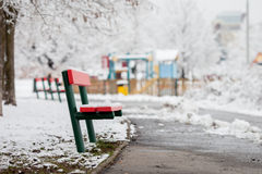 Red bench in a snowy park, children playground in the background Stock Photo