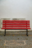 Red bench. Red wooden bench and on the floor, coat of arms made of cobblestones Royalty Free Stock Photos