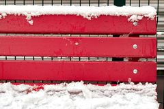 Red benches covered with snow and drops. Water Stock Photo