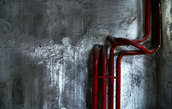 Red bent pipes on concrete walls Royalty Free Stock Photos