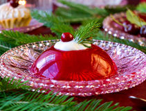Red berries jelly on glass plate with christmas tree Stock Photography