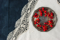 Red berries on the old metal plate on the vintage napkin top view Royalty Free Stock Photography