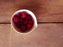 Red berries in  a small white cup on a rough wooden surface. Red berries on a rough wooden surface in the middle of the summer Stock Images