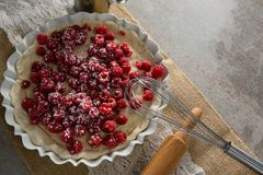Red berries on tart with whisker and rolling pin. Close-up of red berries on tart with whisker and rolling pin royalty free stock photography