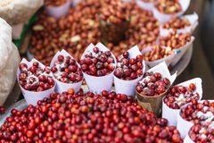 Red Berries topping with salt in paper cone at street local market in Darjeeling. India Royalty Free Stock Photo
