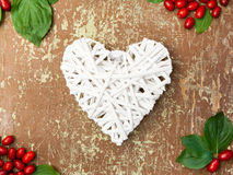 Red berries and white heart shape Royalty Free Stock Photos
