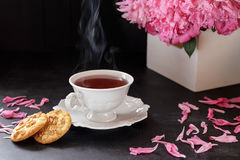 Red berry or fruit tea in teacup with peony. Red berry or fruit tea in white porcelain teacup on black table with peony bouquet and cookies. Hot beverage with Royalty Free Stock Photo
