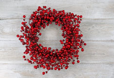 Red berry holiday wreath on rustic white wooden boards Royalty Free Stock Photos