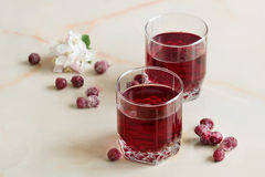 Red berry juice with summer berries on the table. A refreshing summer red berry juice in a glass on a light background Stock Photo