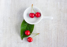 Red berry - sweet cherry in the white gravy boat and green leaf Royalty Free Stock Photos