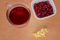 Red berry tea with frozen cranberries. On a wooden background Stock Photos