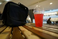 Red beverage and bag on the wood table stock photography