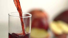 Red beverage is pouring into the empty glass at the background of the blurred fruit. Close-up view. Red beverage is pouring into the empty glass at the stock footage