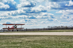 Red Bi-Plane. A red Bi-Plane approaching the runway of a small rural airport Royalty Free Stock Image