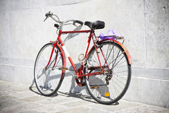 Red bicycle against a marble wall Royalty Free Stock Photos
