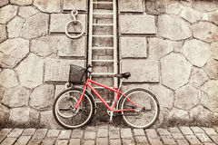 Red bicycle on a background of a stone wall Stock Photography