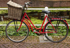 Red Bicycle with Basket Parked Beside Canal in Holland Stock Photography