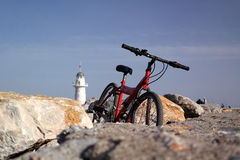 Red bicycle. On the breakwater in the background lighthouse Stock Image